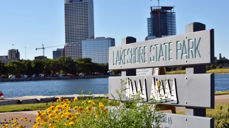 The Lakeshore State Park sign sits in a bed of wild flowers with the city skyline in the background